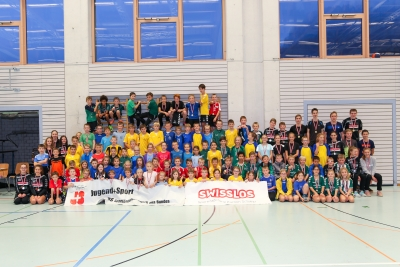Überglückliche junge Handballer präsentieren stolz ihre Medaillen, Pokale und neuen Trainingshosen. (Bild: Esther Heinzer)